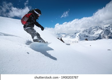 Young woman snowboarder in deep snow - extreme freeride on the background of snow-capped mountains on a sunny day