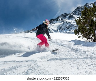 Young woman snowboarder in motion on snowboard in mountains