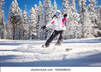 Young woman snowboarder running down the slope in mountains. Winter sport and recreation, leisure outdoor activities.