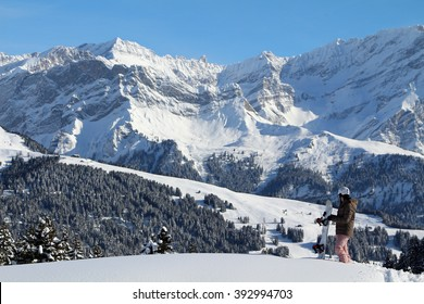 A young woman snowboarder takes in the view of a mountain landscape. Focus on the snowboarder.