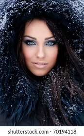 Young woman in a snowy furry hood
