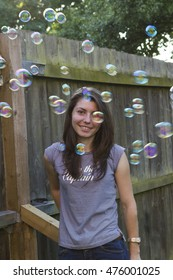 Young woman with soap bubbles in summer evening