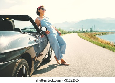 Young woman solo traveler stay near cabriolet car on picturesque mountain road