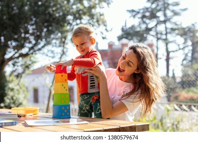 Young Woman and Son  Playing Educational Cube  Toys at Garden