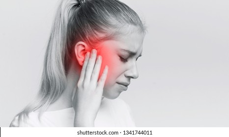 Young woman with sore ear, suffering from otitis, black and white panorama with red accent, free space
