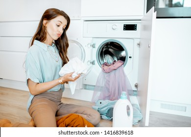 Young woman sorting dirty clothes while sitting on the floor near the washing machine at home