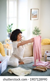 Young woman sorting wardrobe indoors at home, charity donation concept. - Shutterstock ID 1907128990