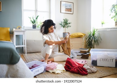 Young woman sorting wardrobe indoors at home, charity donation concept. - Shutterstock ID 1922007524