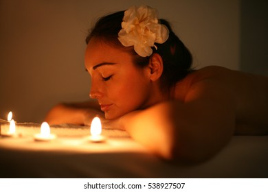 Young woman in a spa center. Lying on a massage table in beautiful surrounding.