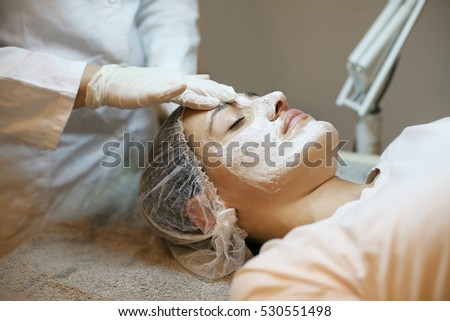 Young woman in a spa center. Lying on a massage table with a mask on her face. Ambient light and pilot lamps used.