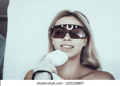 Young Woman in Spa Salon for Laser Hair Removal. Woman in Glasses. Girl in Beauty Salon. Modern Cosmetology. Proffesional Cosmetologist. Doctor with Laser Epilator. Women's Beauty Concept.