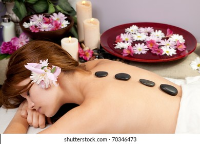 A young woman at a spa waiting for a massage with hot stones on her back.