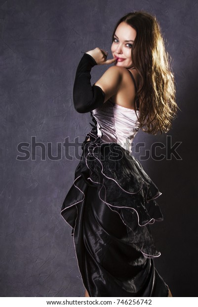 young woman in a Spanish dress dancing on a gray background