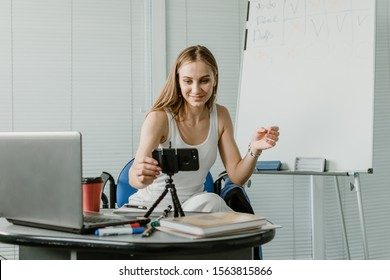 Young woman speaking in front of camera for vlog as blogger. Caucasian businesswoman working, recording video tutorial at office. Earn extra money, Side hustle, money making, turning hobbies into cash