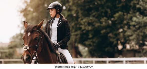 Young woman in special uniform and helmet riding horse. Equestrian sport - dressage.