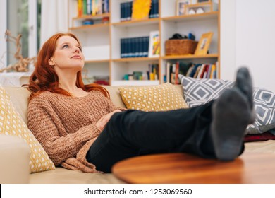 Young woman spending quality time relaxing at home with her feet up lookig into the air with a dreamy expression in a low angle view