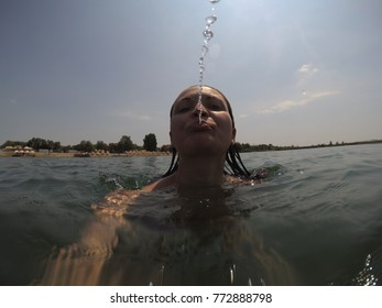 a young woman spits on the camera while swimming on the water