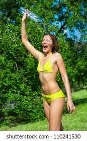 Young woman splashing herself with water outdoors