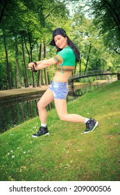 young woman in sport dress dancing in reggaeton or hiphop style in the park
