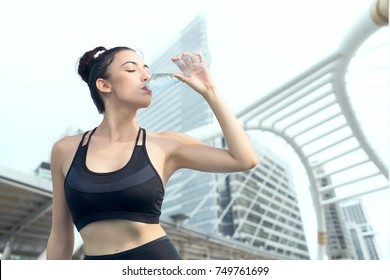 Young woman in sport dresses is drinking water with cityscape background, sport and healthy concept.