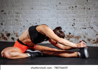 Young woman sport stretching in gym with brick wall and black mats