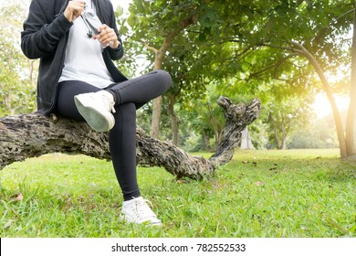 young woman sport ware sit in the park relax herself and drink water