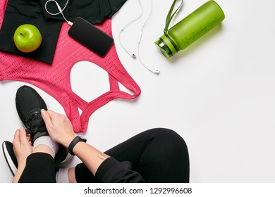 Young woman in sporting leggings laces sneakers, preparing for training. Accessories for sports on white background flat lay top view.
