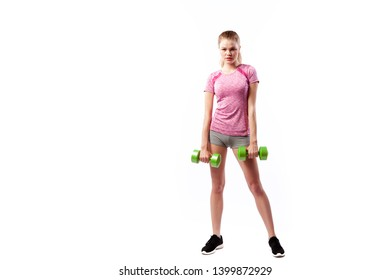Young woman in sports clothes smilling and doing exercises on biceps with dumbells on white isolated background. Side view.Fit girl living an active lifestyle