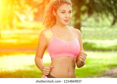 Young woman sports, running in the park. Girl model runs at sunrise or sunset outdoors. Healthy lifestyle, jogging.