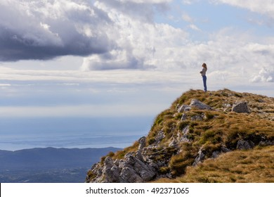 A young woman in a sports suit stands on a cliff high in the mountains with beautiful clouds on the background