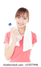 Young woman in sports wear drinking water