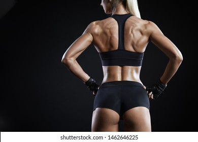 Young woman in sports wear with muscular body.  Close-up shot of back of female fitness model three quarter on black with copy space. Beautiful fitness, great design for any purposes.