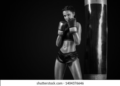 Young woman sportsman boxer doing boxing training at the gym. Girl wearing gloves, sportswear and hitting the punching bag. Isolated on black background with smoke. Copy Space.