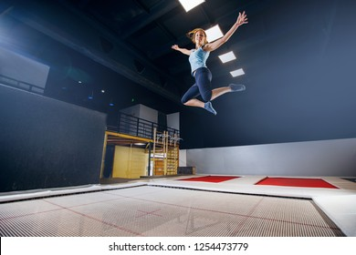 Young woman sportsman fitness jumping on club trampoline and doing split