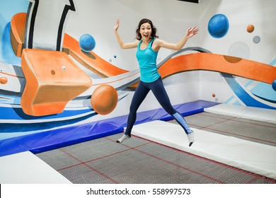 Young woman sportsman jumping on a trampoline in fitness park and doing exersice indoors