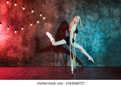 Young woman in sportswear with crutch and broken leg dances against the background of a wall