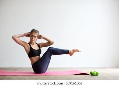 Young woman in sportswear, doing fitness exercise with dumbbell, at home.