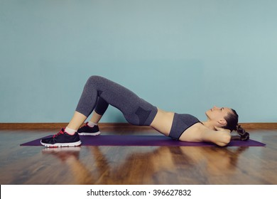 Young woman in sportswear doing sport at home