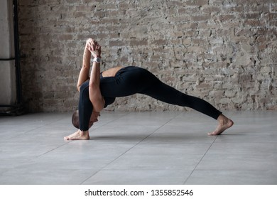 young woman in sportswear doing yoga stretching exercise - high lunge with twist on stone floor