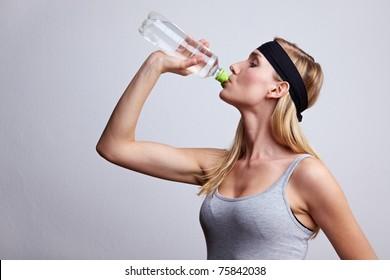 Young woman in sportswear drinking water from a plastic bottle