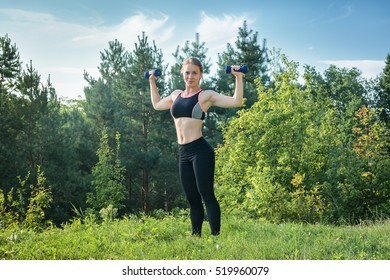 Young woman in sportswear is engaged in sports with dumbbell in nature. Healthy lifestyle. Layout