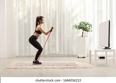 Young woman in sportswear exercising with a resistance band in front of a tv at home