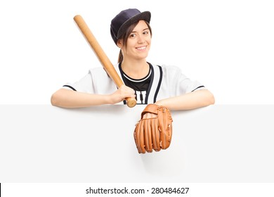 Young woman in sportswear holding a baseball bat and wearing a baseball glove and posing behind a blank signboard isolated on white background