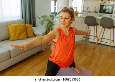 Young woman in sportswear making Warrior yoga exercise at home. Young woman exercising at home due to COVID 19 pandemic.