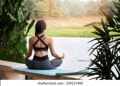 young woman in sportswear meditating while sitting in lotus pose on yoga mat