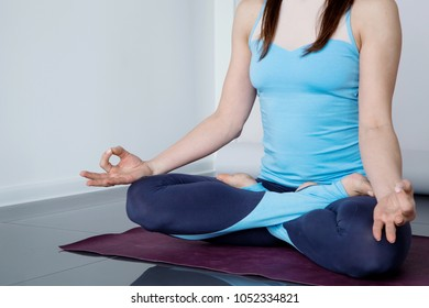 Young woman in sportswear practicing Gyan mudra(wisdom, knowledge) with copy space. Smiling young woman doing morning yoga practice. Healthy and sport lifestyle, working out, wearing sportswear.