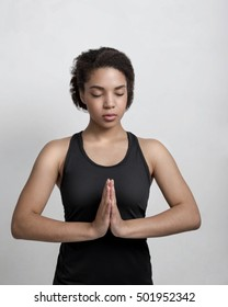 Young woman in sportswear practicing yoga at home