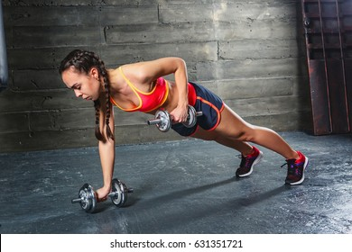 Young woman in sportswear Push-up with dumbbells in hands in a dark gym