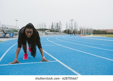 Young woman in sportswear ready to run on sports ground.