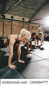 Young woman in sportswear smiling while doing pushups with a group of friends during a workout class at the gym